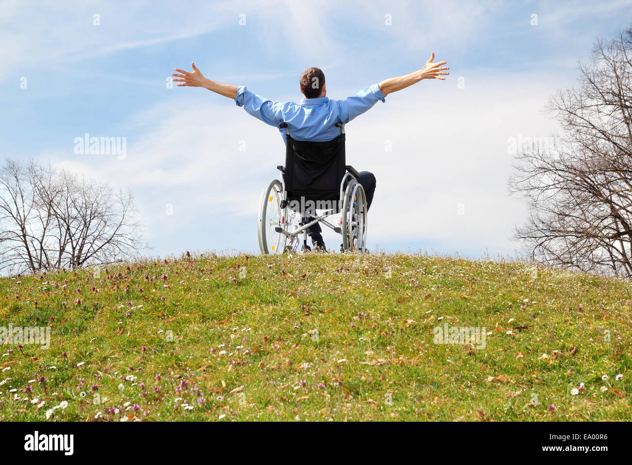 Happy Wheelchair user on a green hill - Stock Image