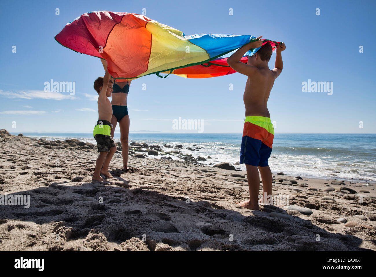 Mature woman and two sons holding up multi colored textile on beach, County Park, Los Angeles, California, USA - Stock Image