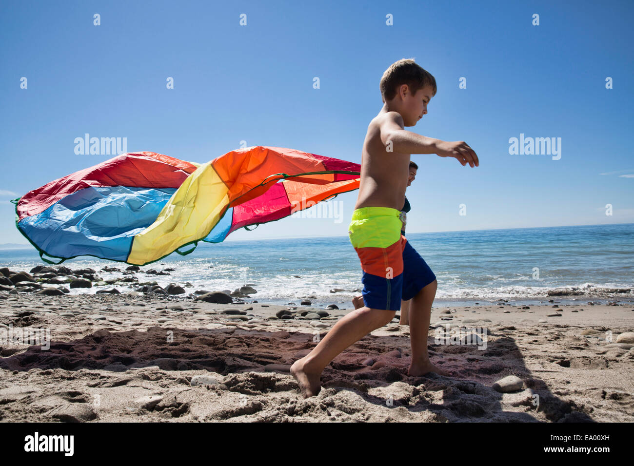 Mother and son running with multi colored textile on beach, County Park, Los Angeles, California, USA - Stock Image