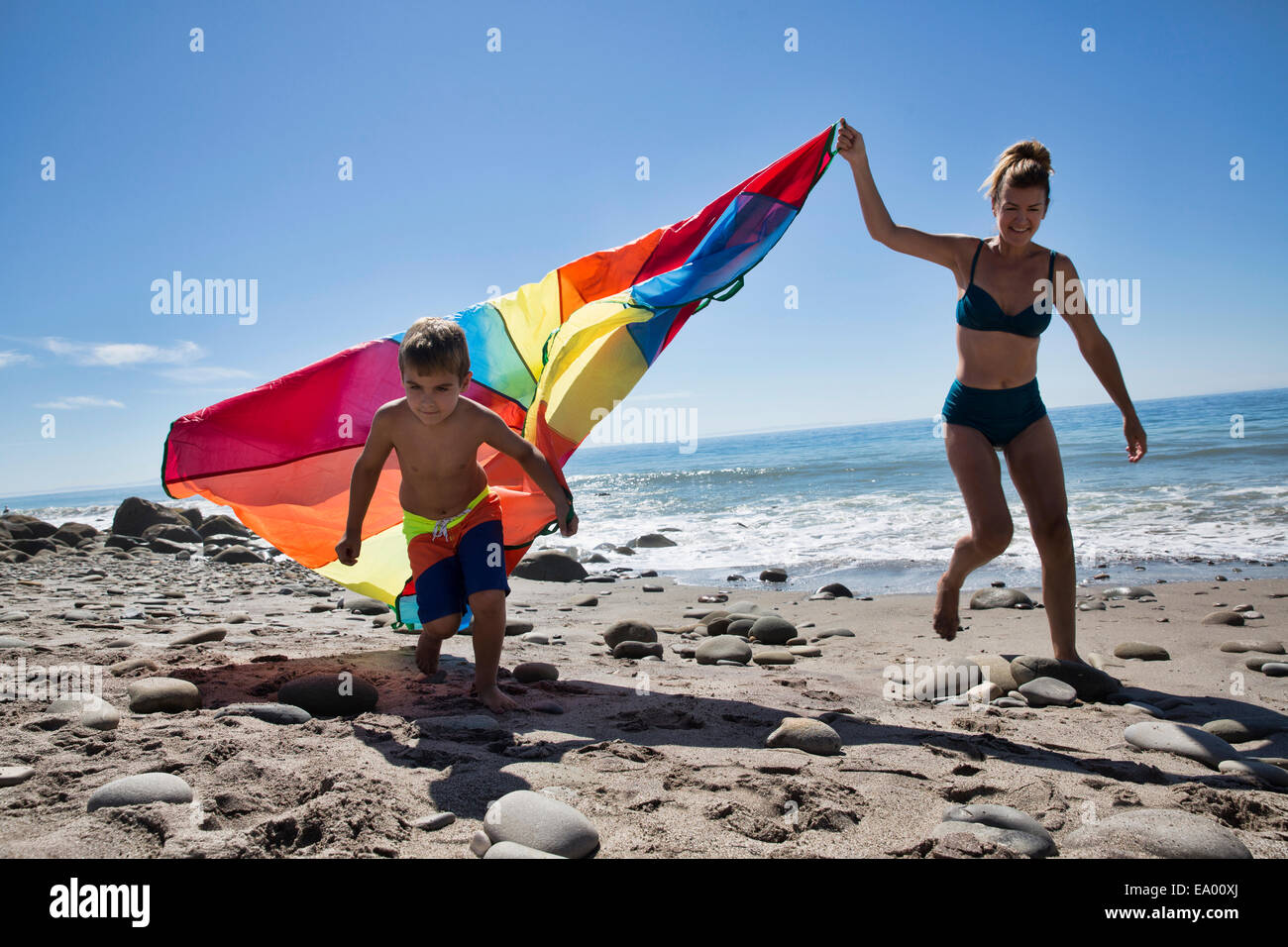 Mature woman and son running with multi colored textile on beach, County Park, Los Angeles, California, USA - Stock Image