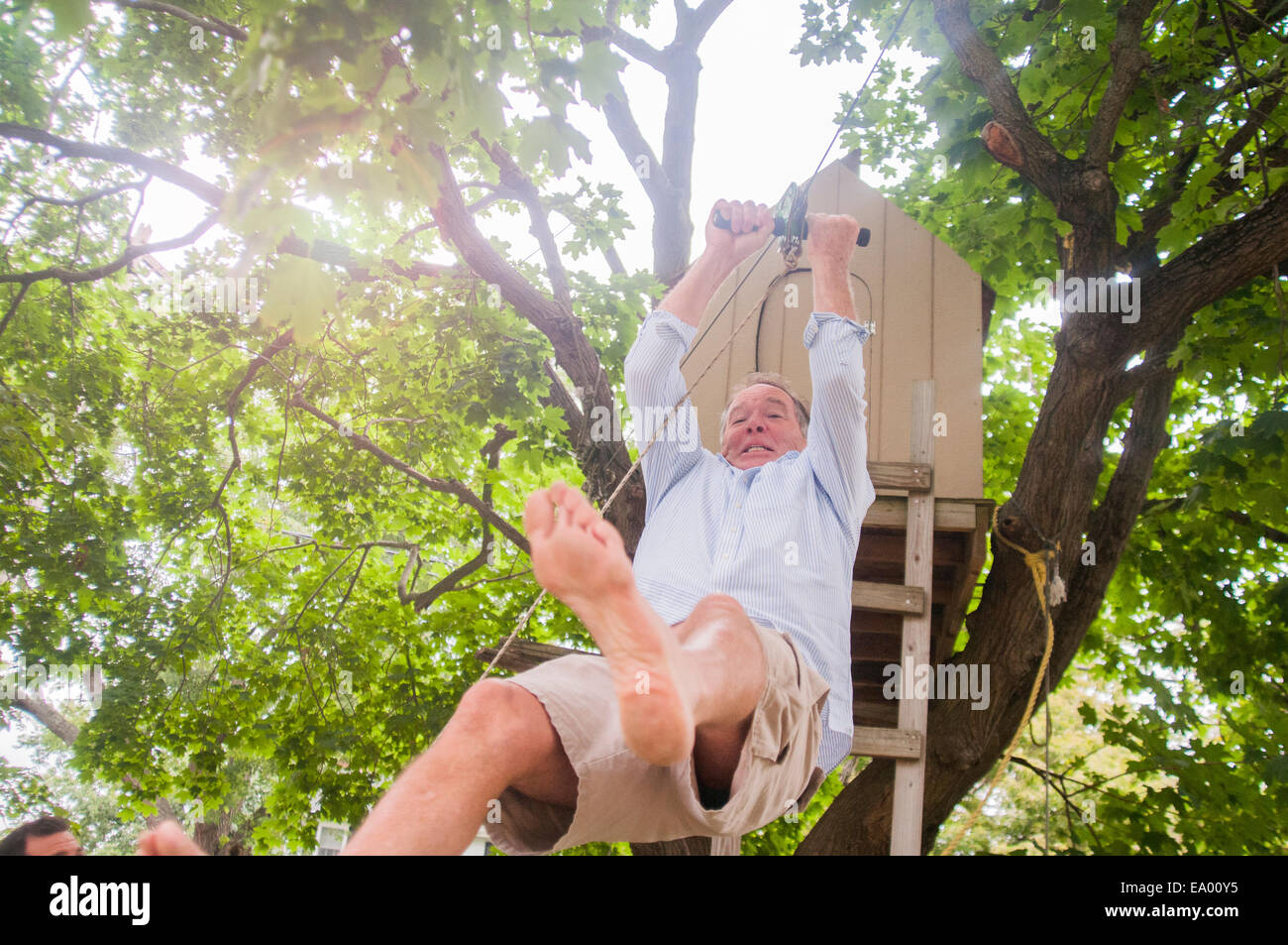 Mature man sliding down on pulley from tree house - Stock Image