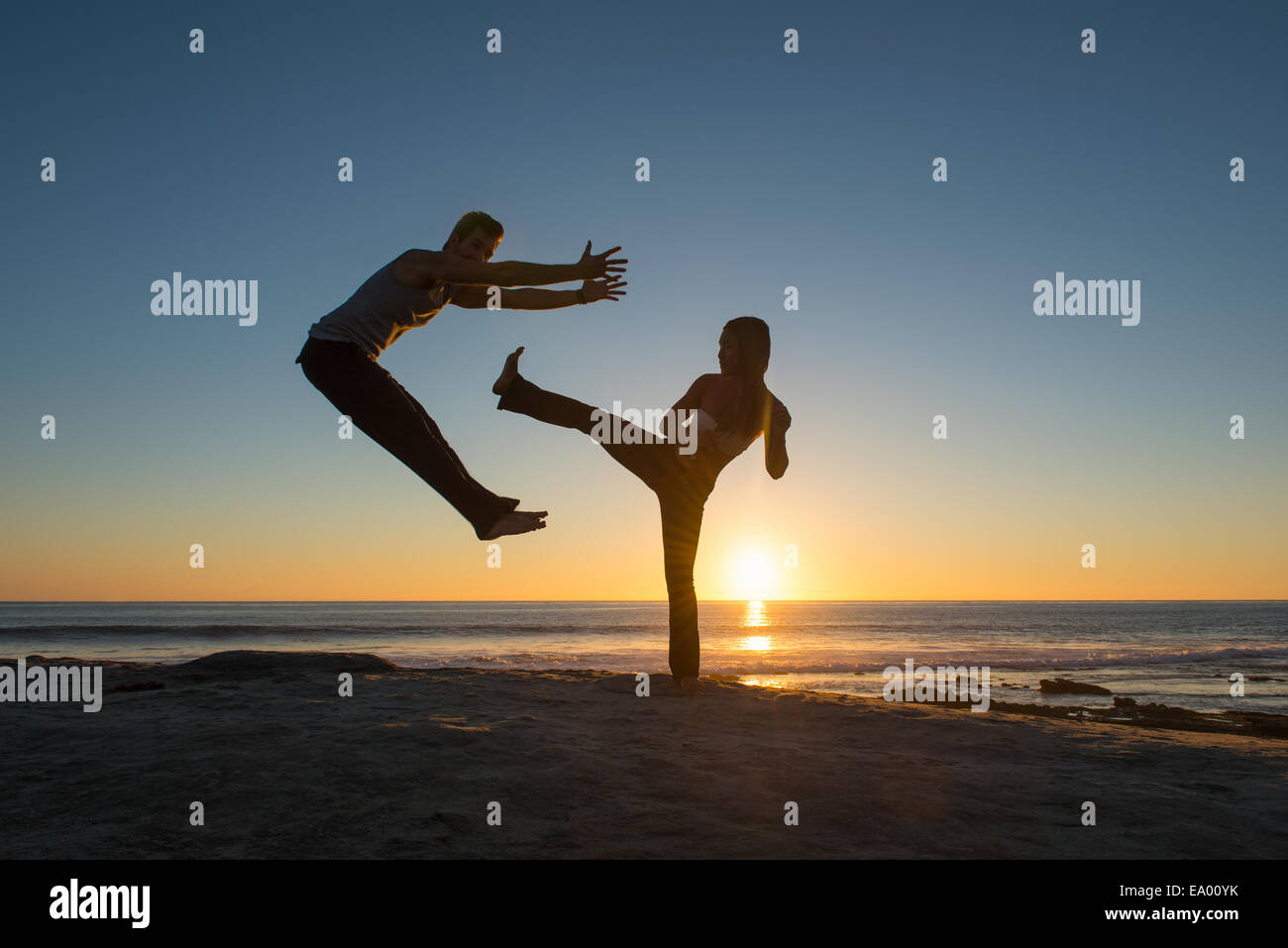 People in jumping and kicking poses on Windansea beach, La Jolla, California - Stock Image
