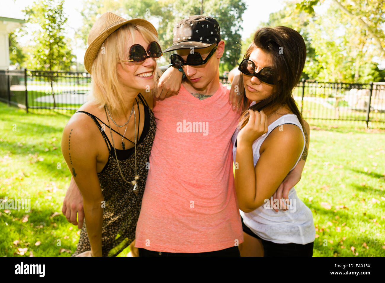 Portrait of young man and two female friends in upside down sunglasses - Stock Image