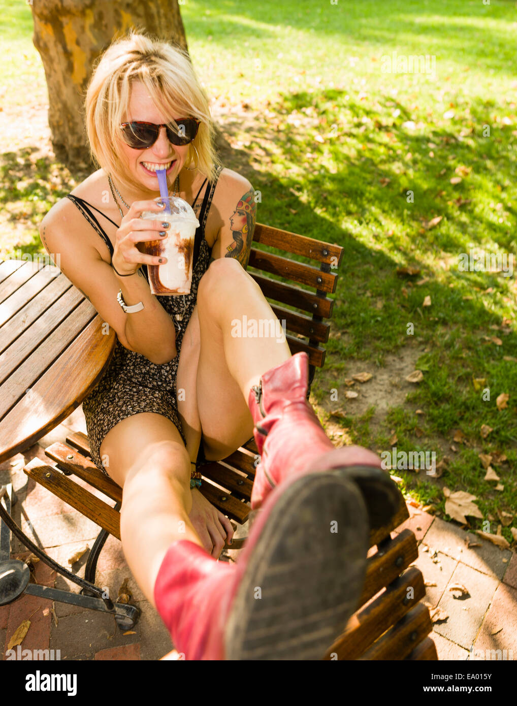 Portrait of young woman in park drinking frappe - Stock Image