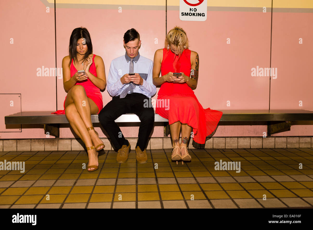 Three young adult friends texting on smartphones whilst sitting in subway station - Stock Image