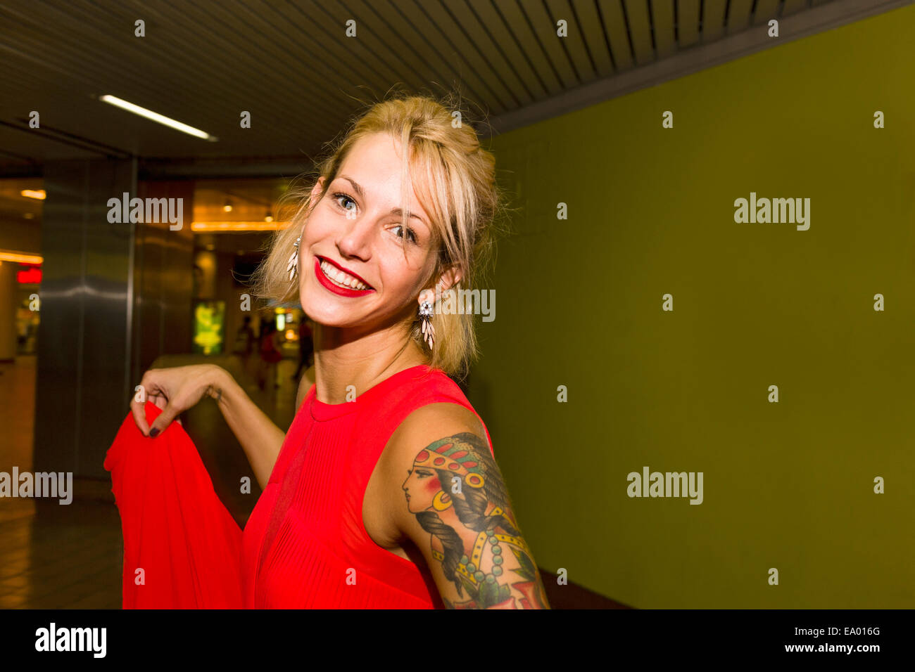 Portrait of young woman wearing red dress in subway station Stock Photo