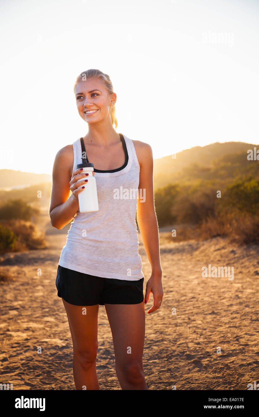 Young female jogger holding water bottle, Poway, CA, USA - Stock Image