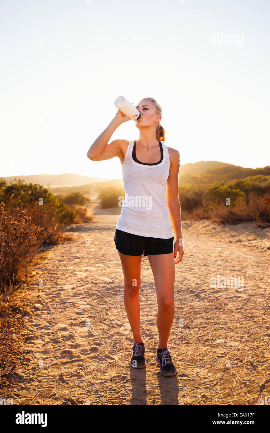 Female jogger drinking from water bottle, Poway, CA, USA - Stock Image