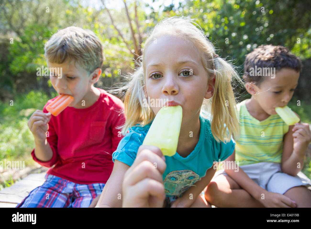 Portrait of three children in garden eating ice lollies Stock Photo