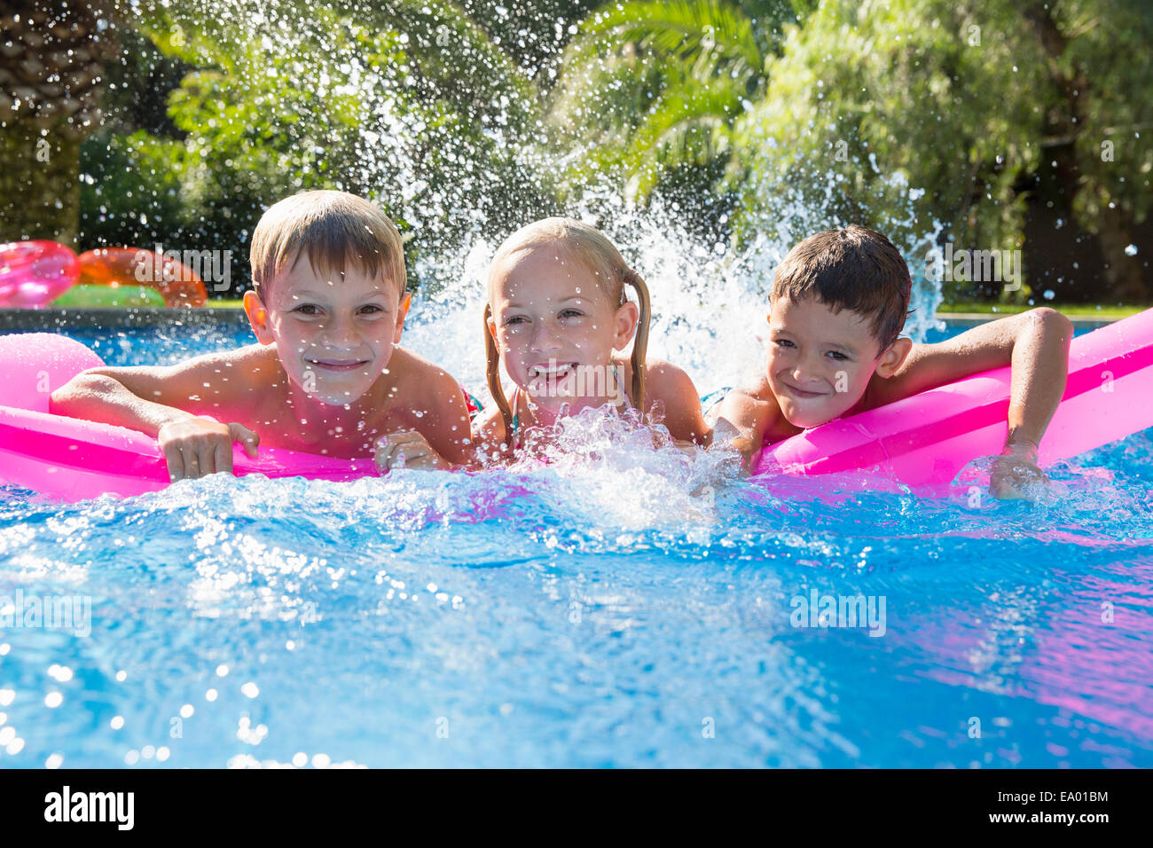 Portrait of three children splashing on inflatable mattress in garden swimming pool - Stock Image
