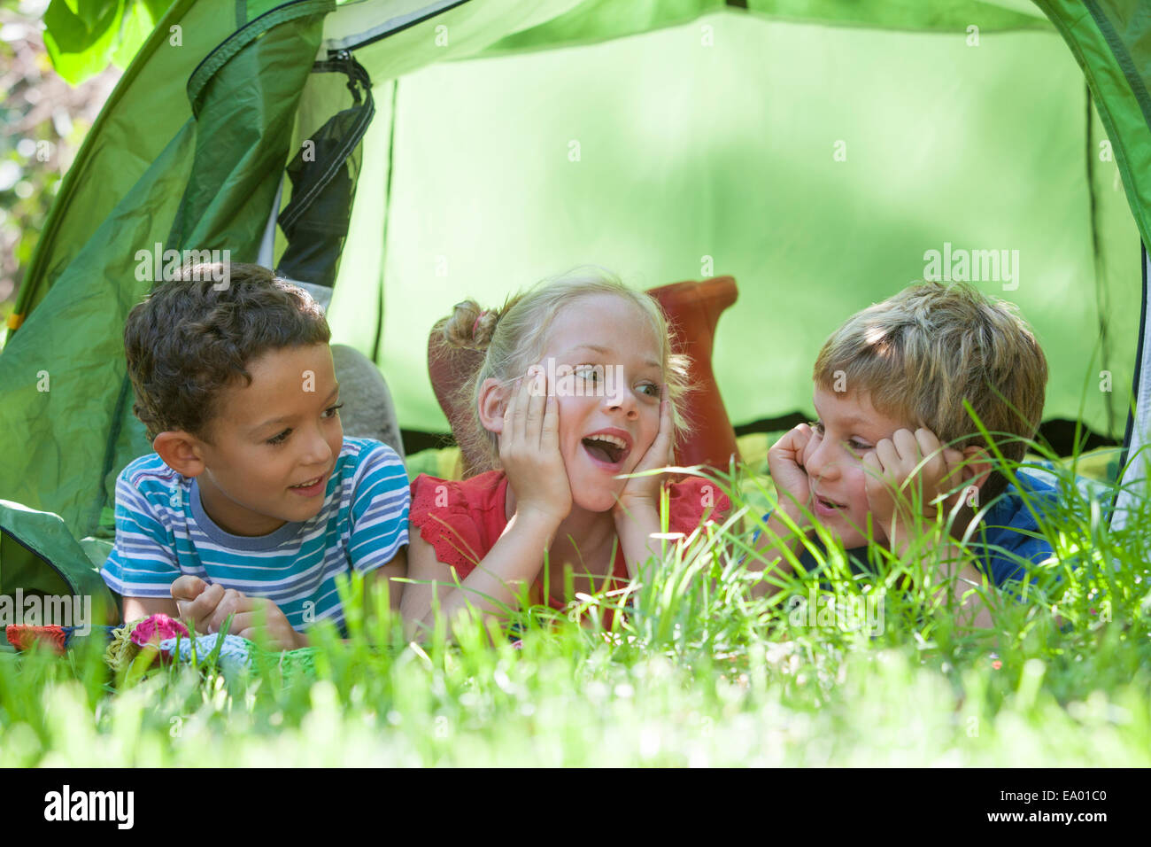 Three children lying chatting in garden tent - Stock Image