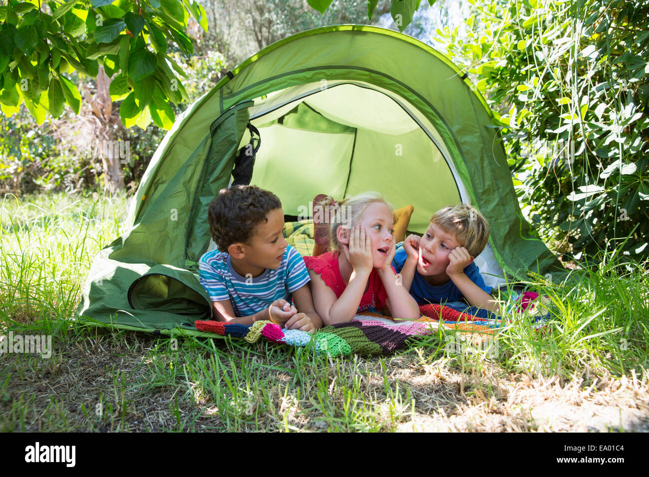 Three children chatting in garden tent - Stock Image
