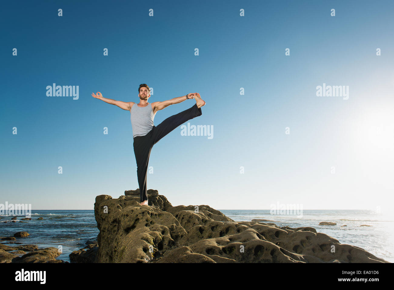 Standing Big Toe pose - Utthita Hasta Padangusthasana, Windansea beach, La Jolla, California - Stock Image