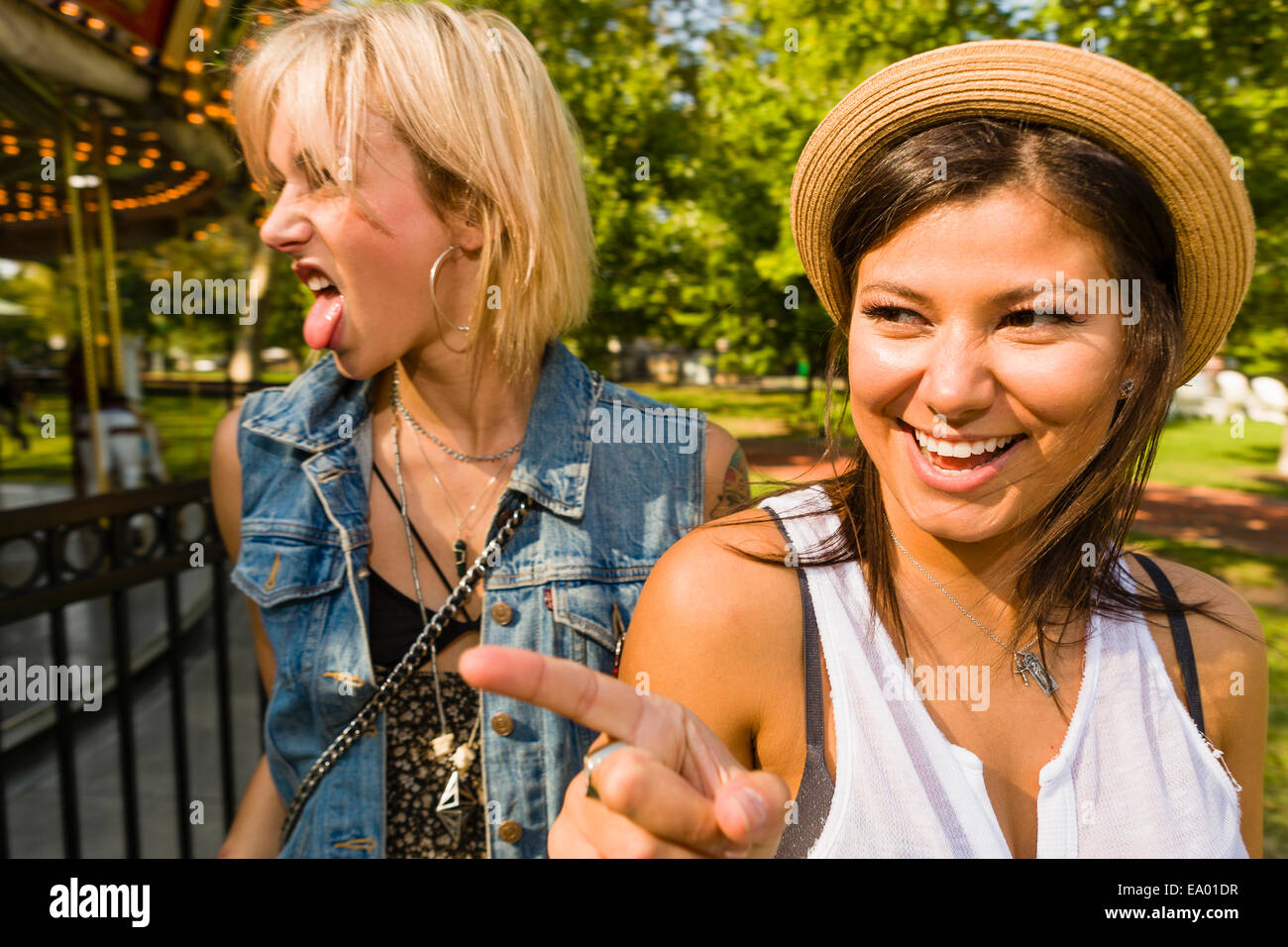 Two young women pointing and sticking out tongue in park - Stock Image