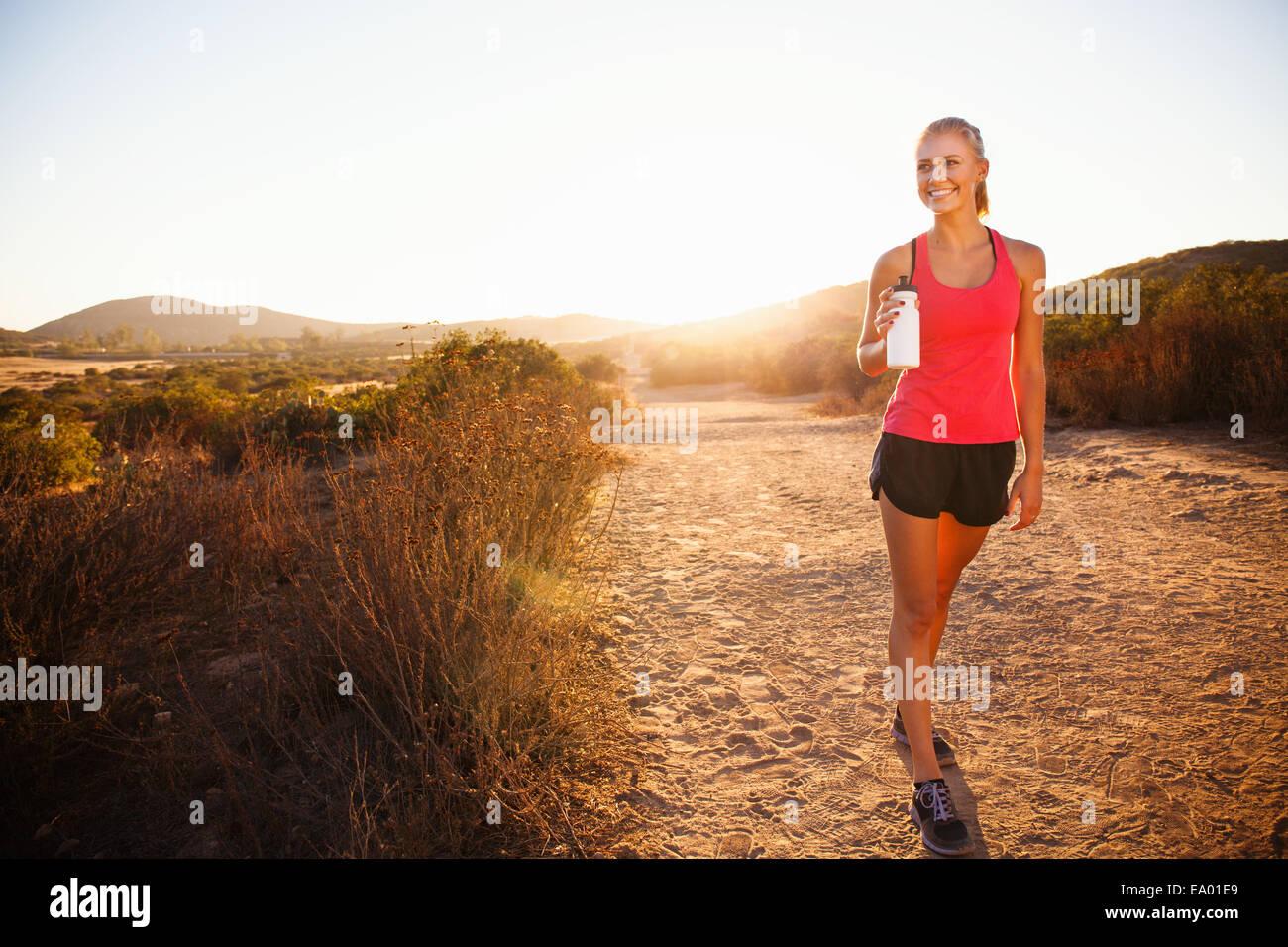 Female jogger holding water bottle on path, Poway, CA, USA - Stock Image