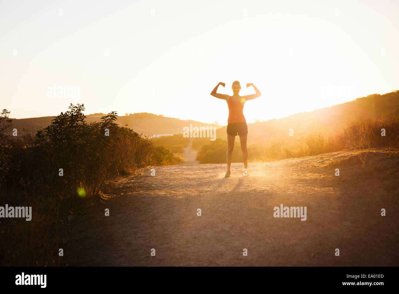 Female jogger flexing arms in sunlight, Poway, CA, USA - Stock Image