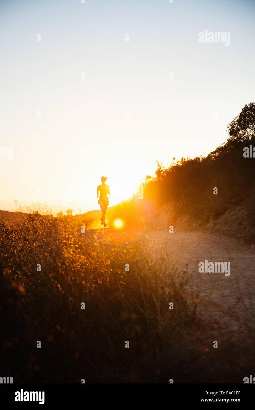 Female jogger running in sunlight, Poway, CA, USA - Stock Image