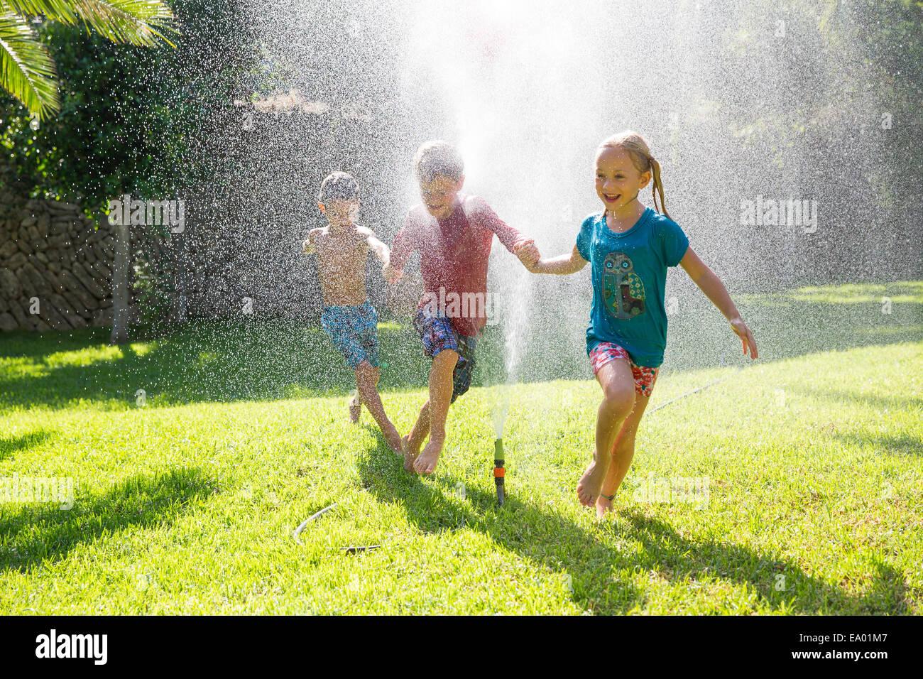 Three children in garden running through water sprinkler - Stock Image