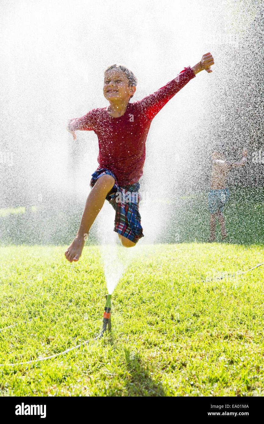 Boy jumping over water sprinkler in garden - Stock Image