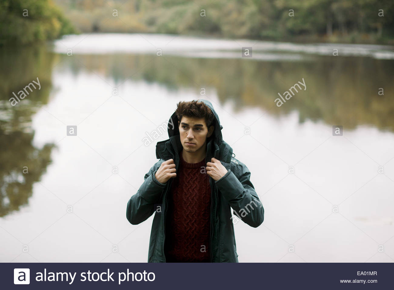 Young man standing looking away from riverbank - Stock Image