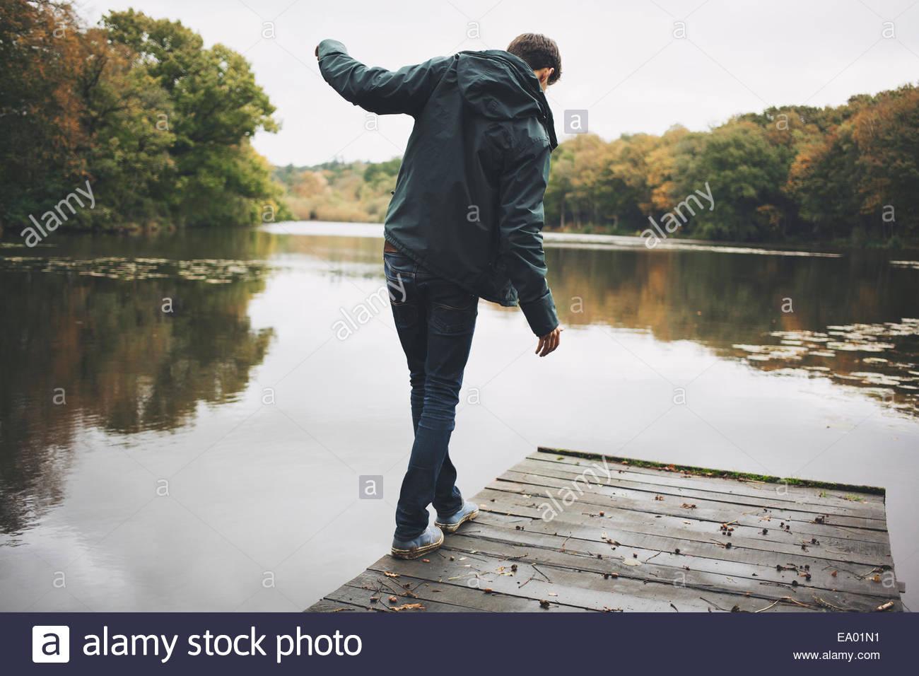 Young man walking along edge of river pier - Stock Image