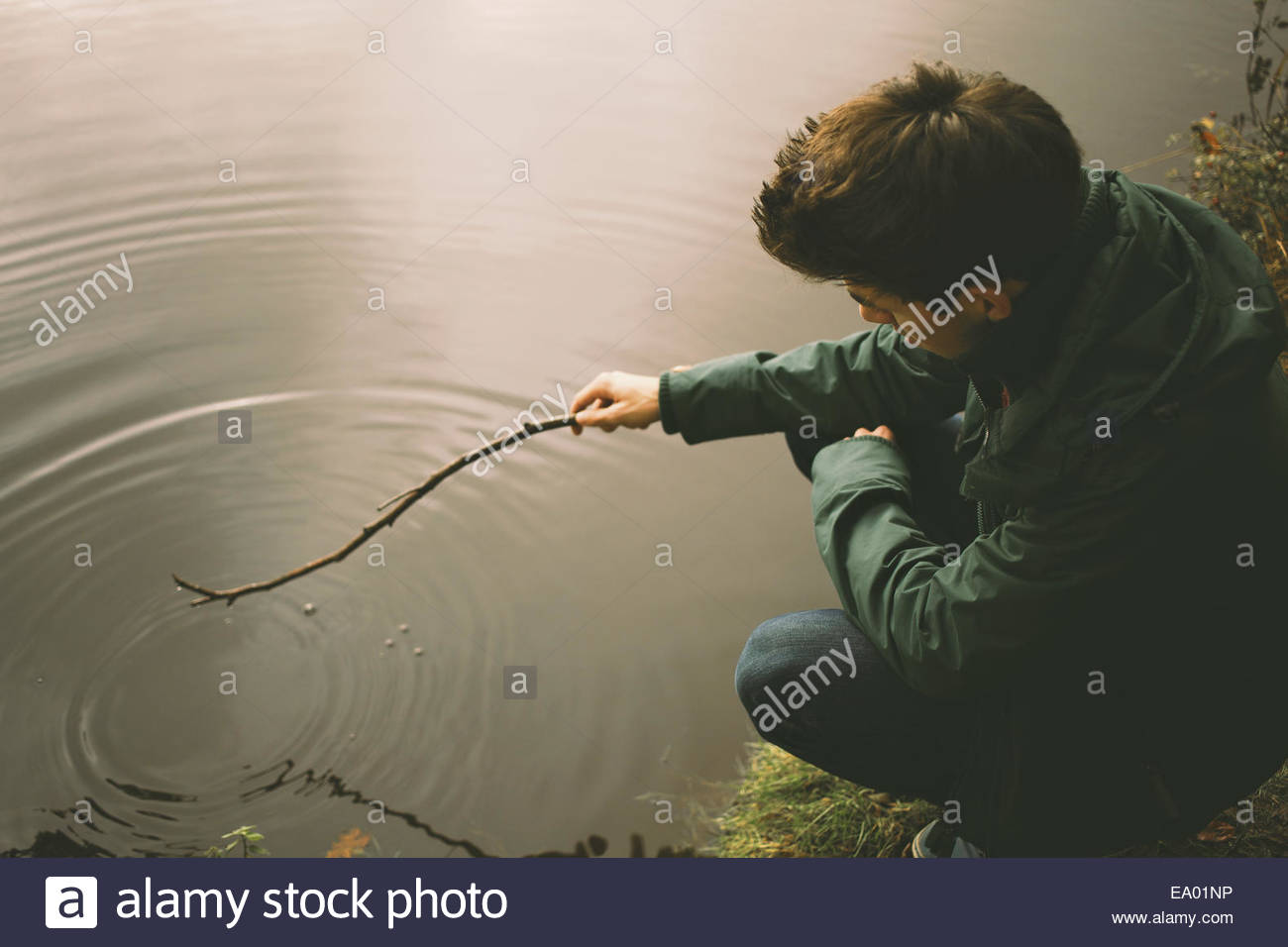 Young man crouching on riverbank making ripples in water with twig - Stock Image