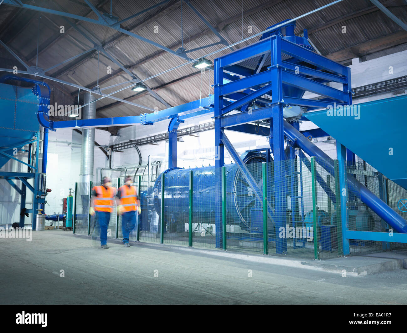 Workers checking metal ore grinding mill - Stock Image