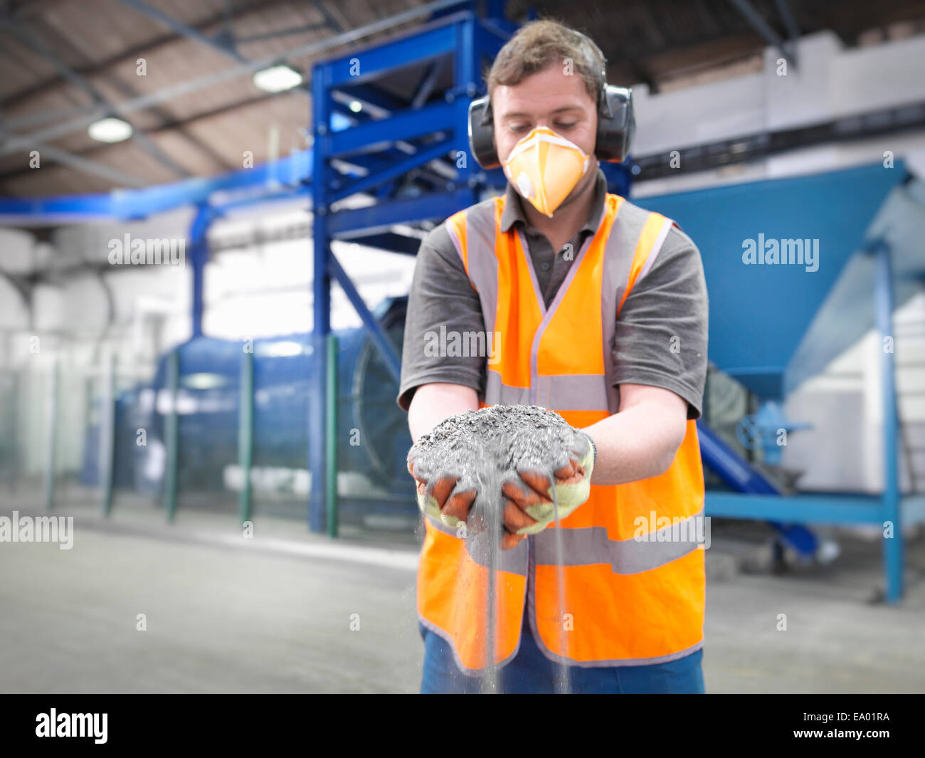 Worker with handful of ground metal ore in grinding mill - Stock Image