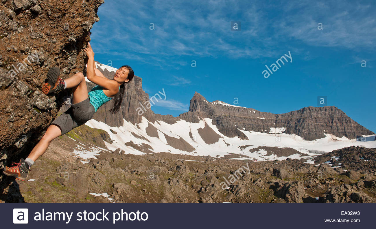 Female climber climbing boulder with Dyrfjoll at the horizon, East Iceland, Iceland - Stock Image