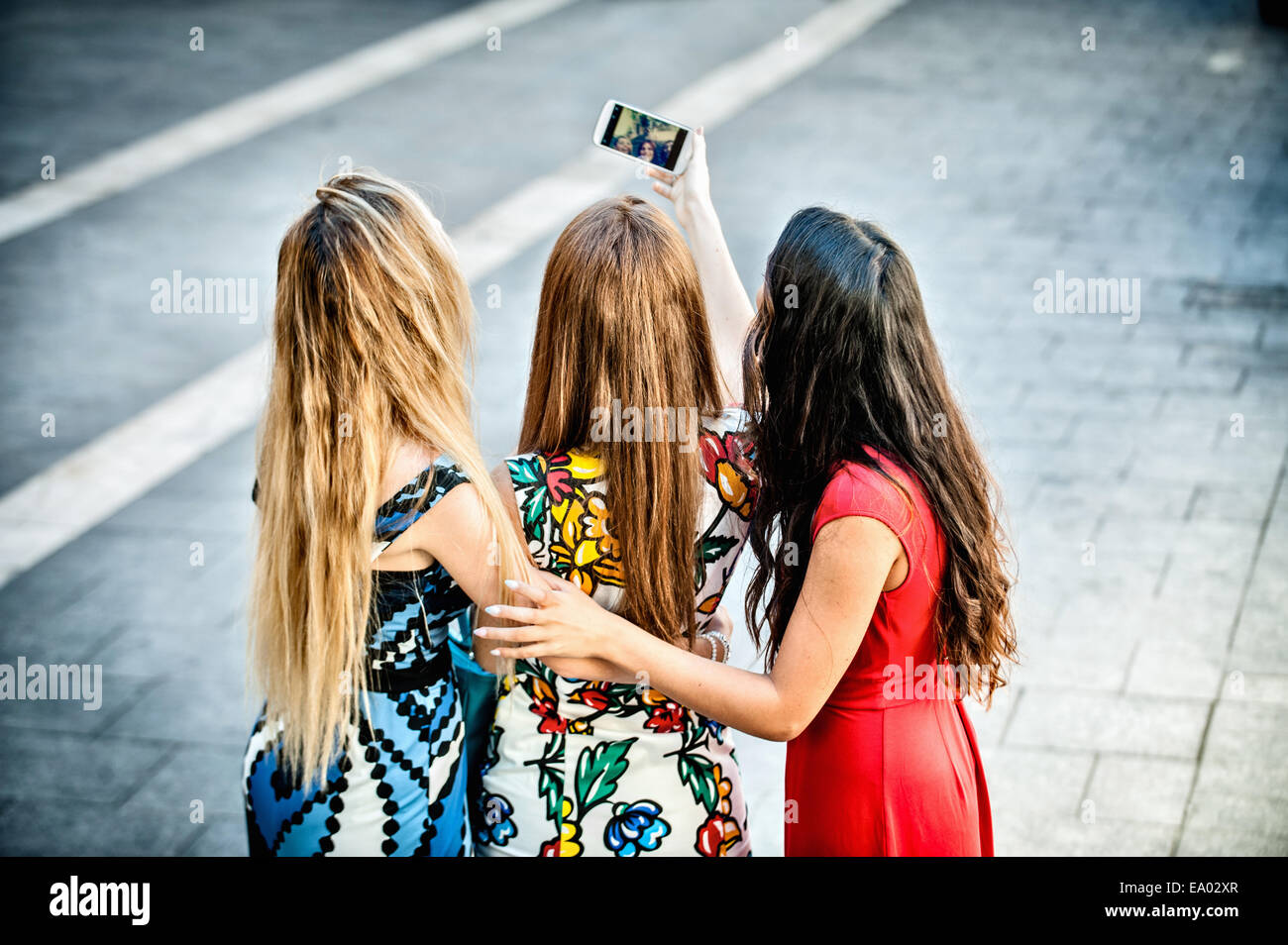 Rear view of three young women taking selfie with smartphone, Cagliari, Sardinia, Italy - Stock Image