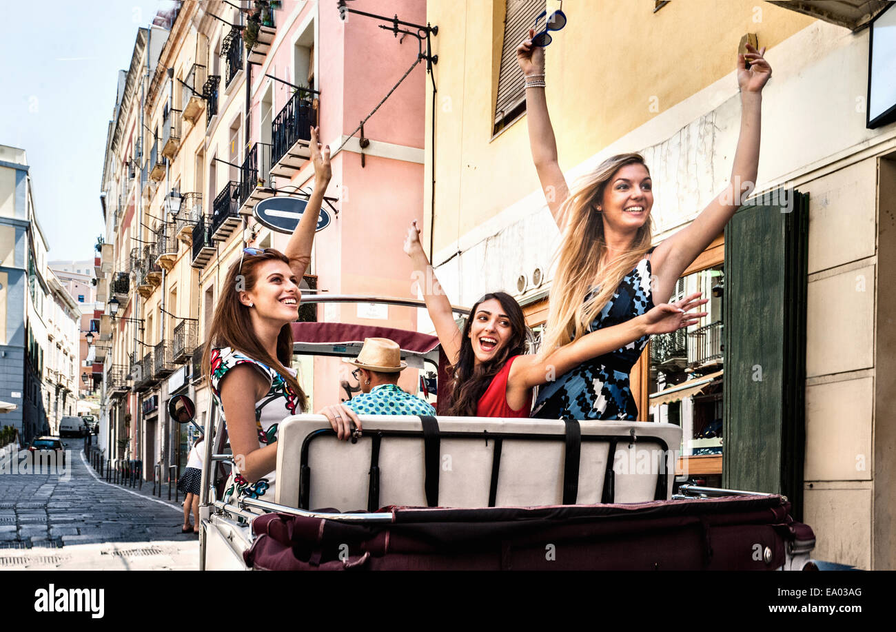 Three young women in open back seat of Italian taxi, Cagliari, Sardinia, Italy Stock Photo