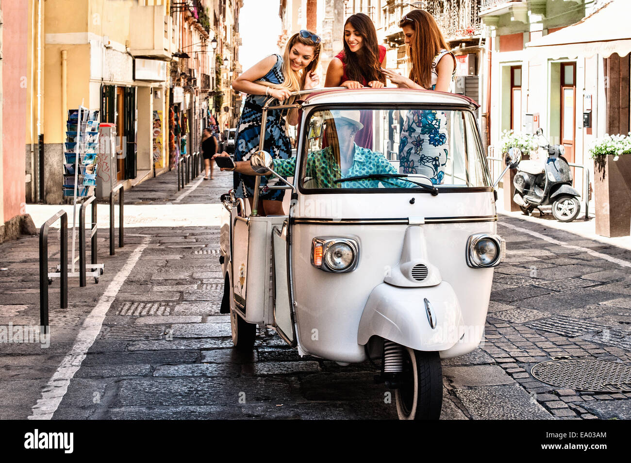 Three young women standing up in open back seat of Italian taxi, Cagliari, Sardinia, Italy - Stock Image