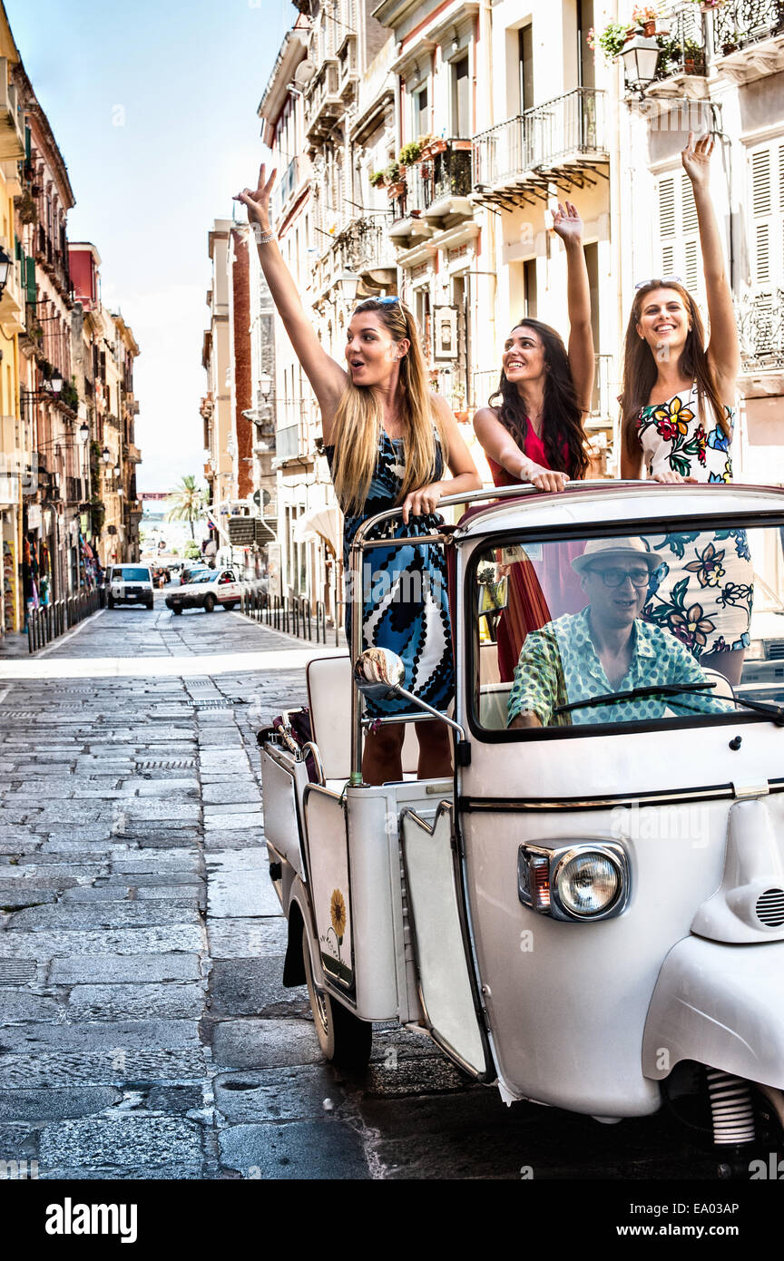 Three young women waving from open back seat of Italian taxi, Cagliari, Sardinia, Italy - Stock Image