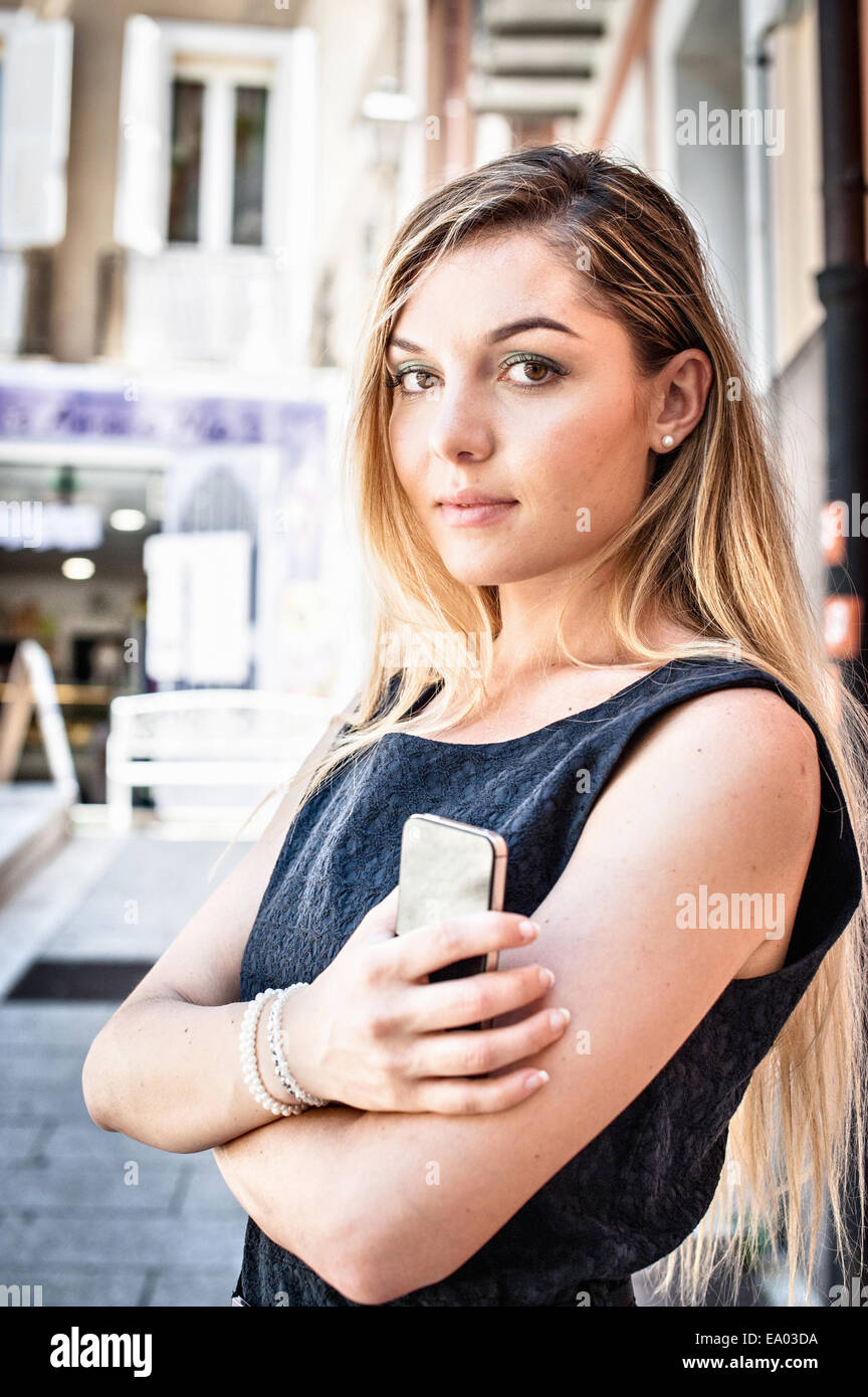 Portrait of confident young woman on city street - Stock Image