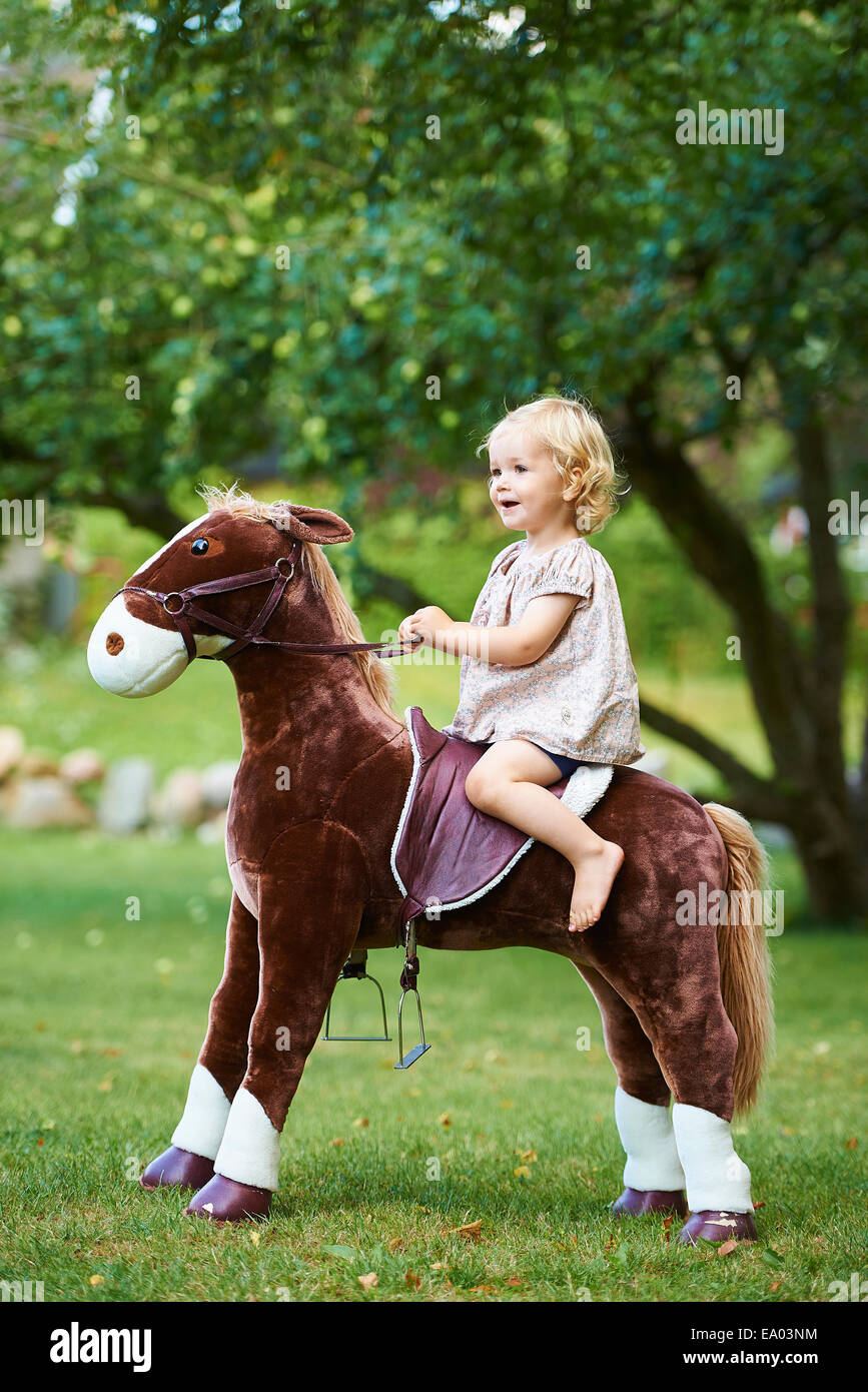 Portrait of female toddler riding toy horse in garden - Stock Image