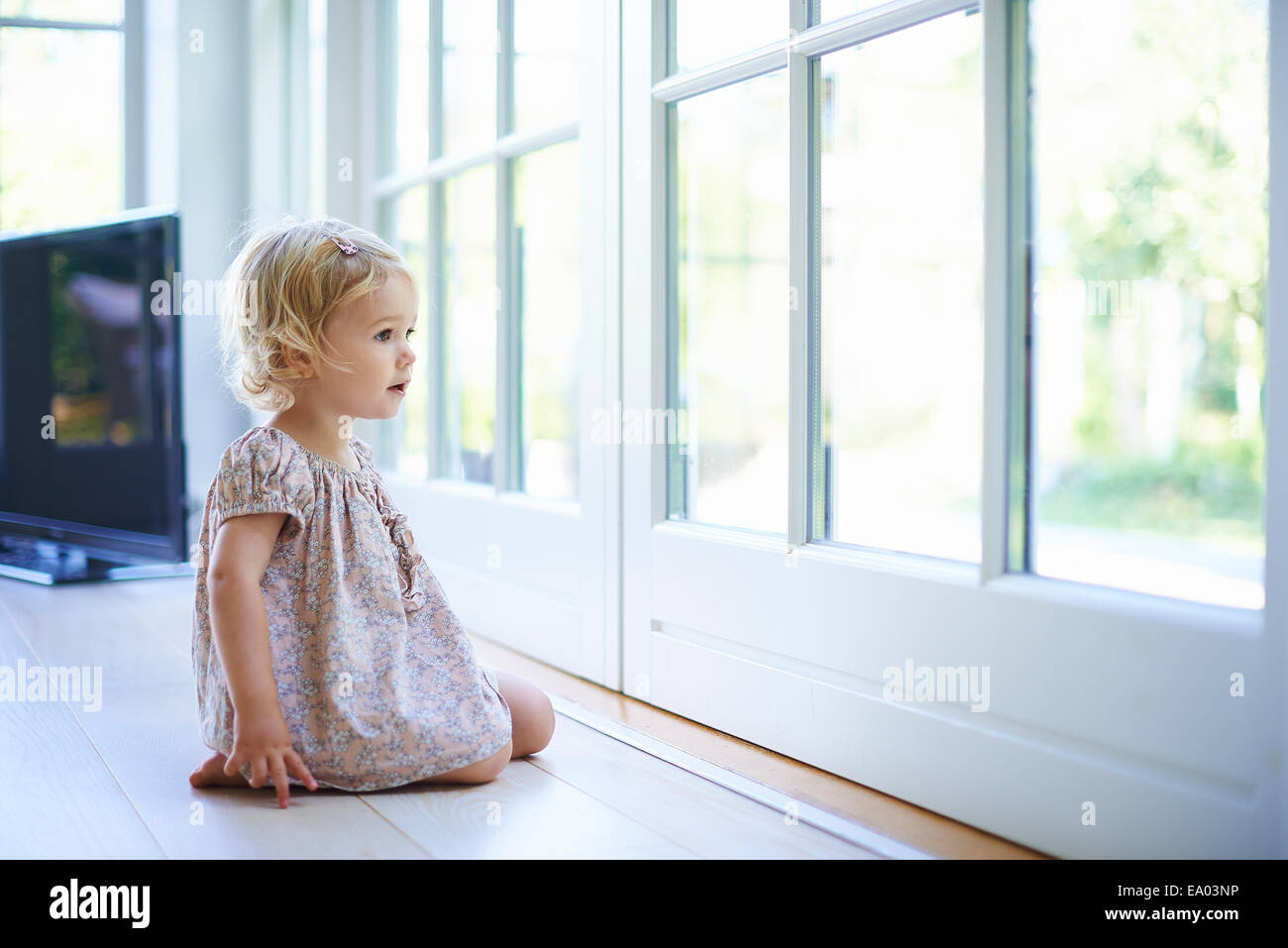 Portrait female toddler sitting on floor looking out of patio doors Stock Photo