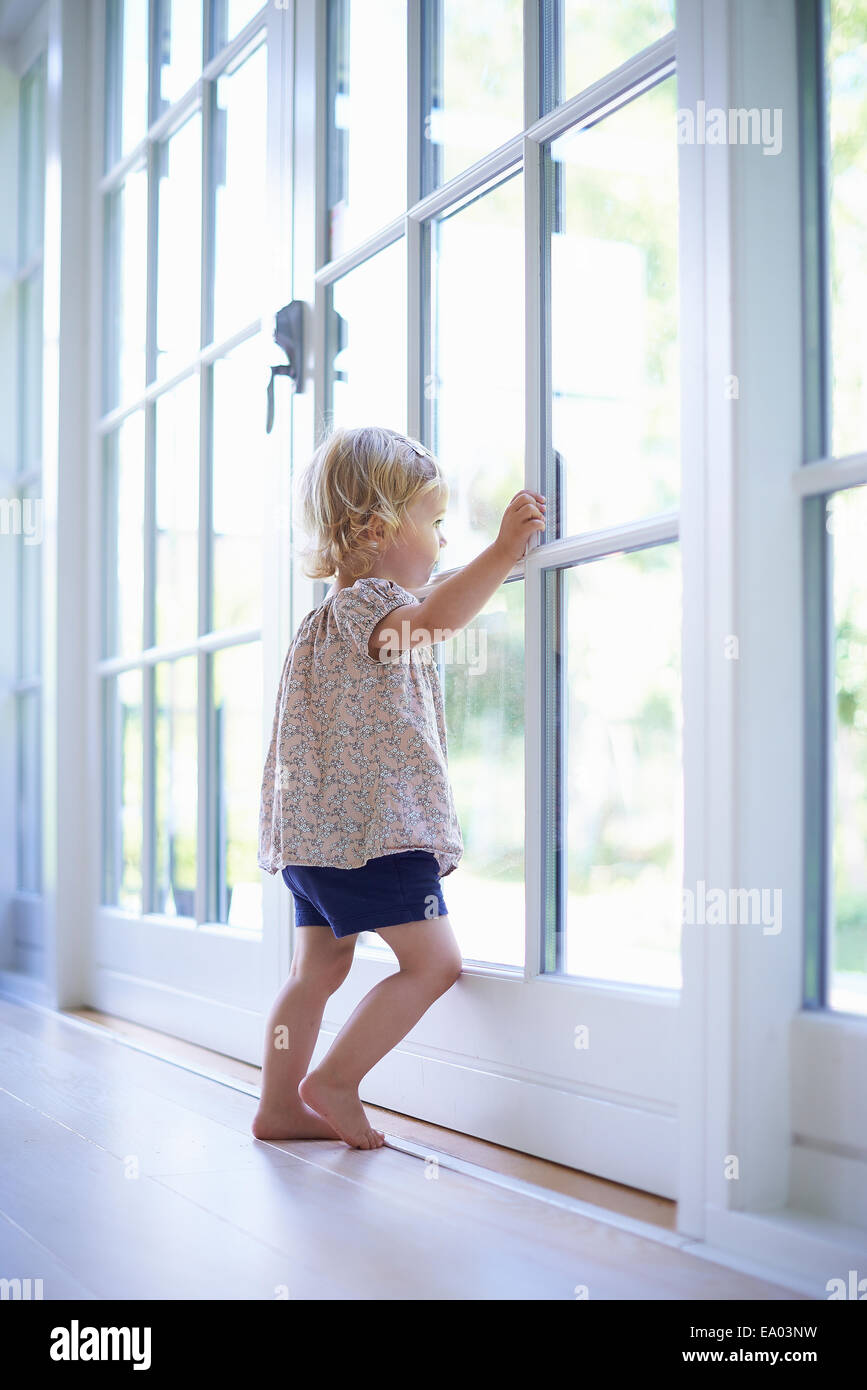 Portrait female toddler looking out of patio doors - Stock Image