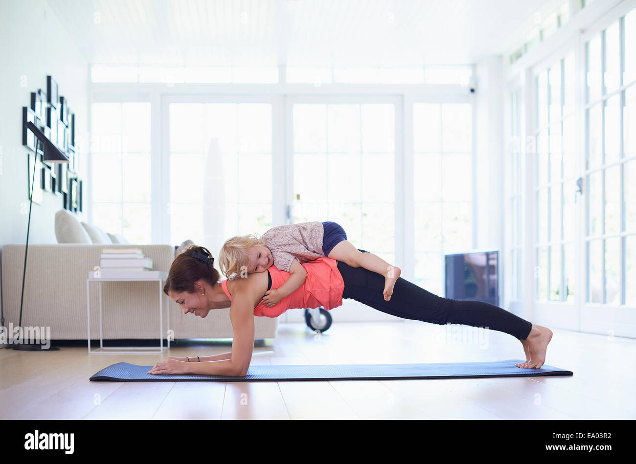 Mid adult mother practicing yoga with toddler daughter on top of her - Stock Image
