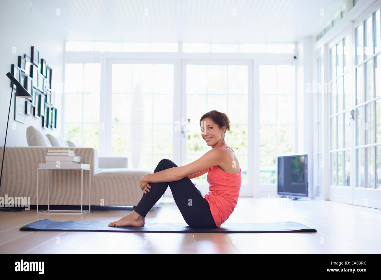 Portrait Of Mid Adult Woman On Yoga Mat In Living Room