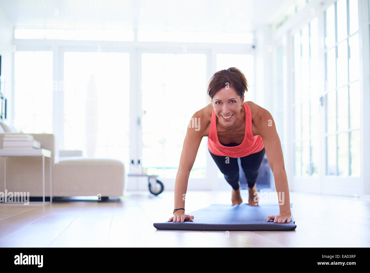Mid adult woman doing press ups in living room - Stock Image