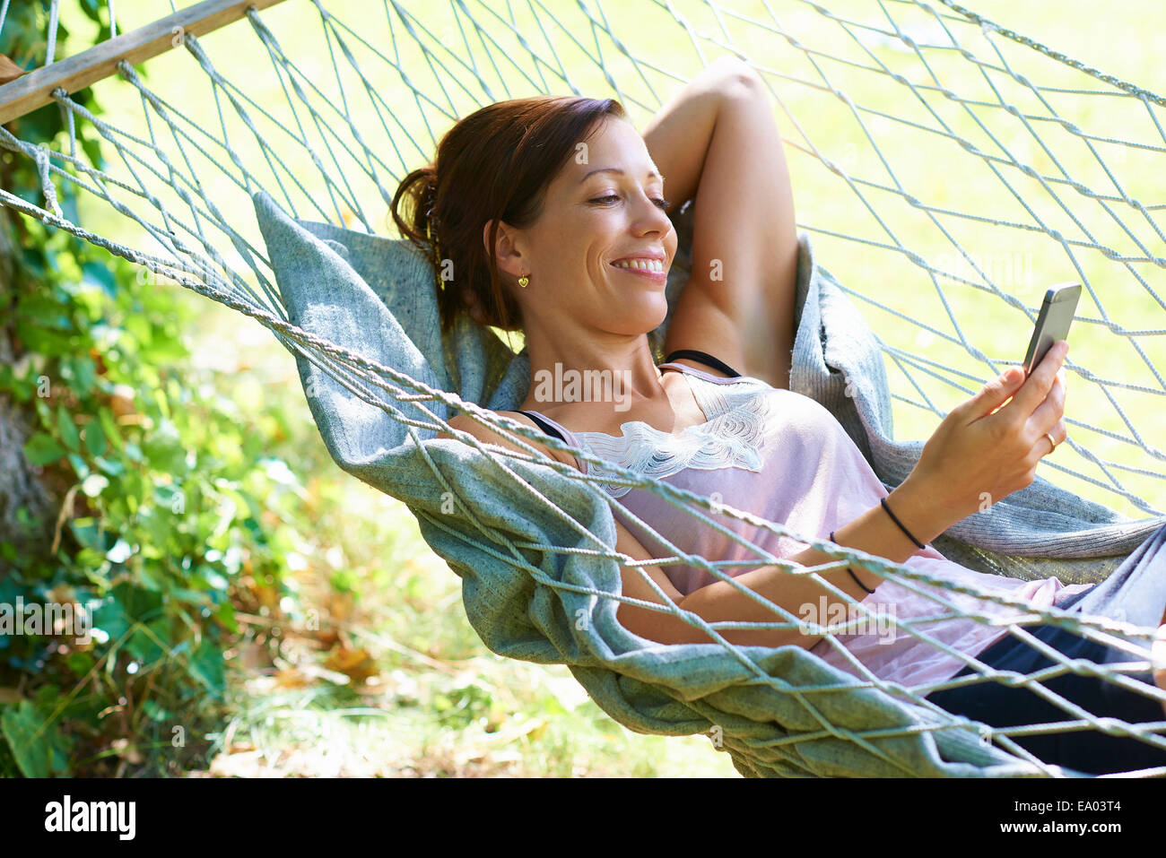Mid adult woman reclining in garden hammock looking at smartphone - Stock Image