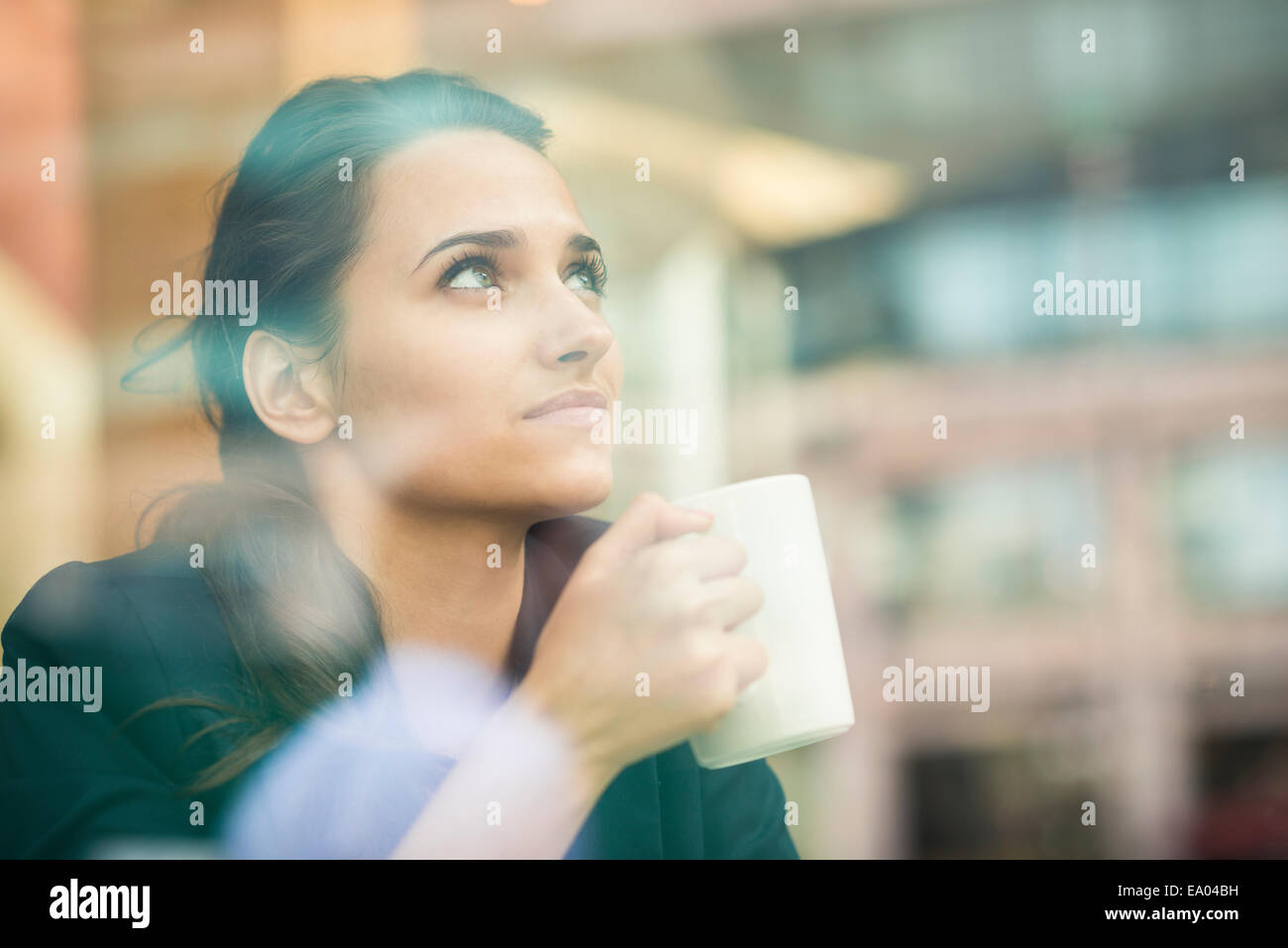businesswoman drinking coffee and looking out of cafe window, London, UK - Stock Image
