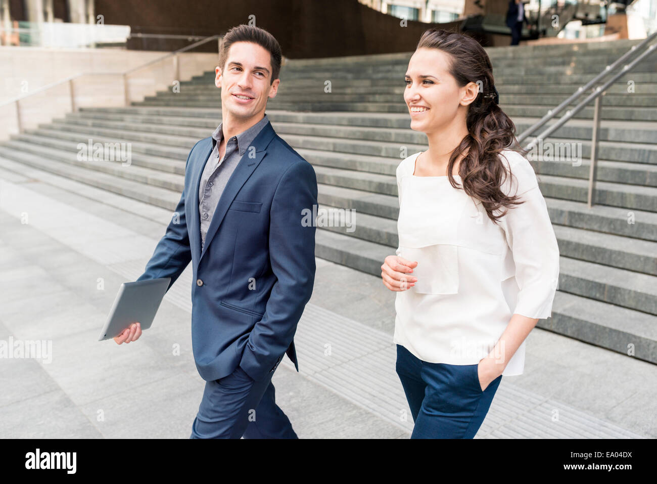 Young businessman and woman chatting whilst walking, London, UK - Stock Image