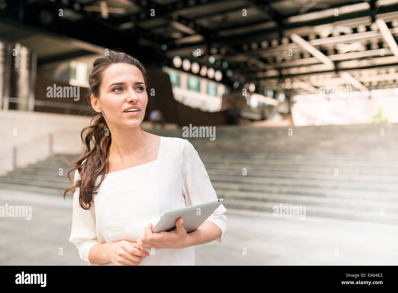 businesswoman waiting outside station with digital tablet, London, UK - Stock Image