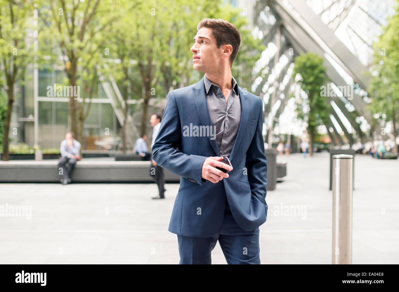 Worried looking young businessman at Broadgate Tower, London, UK - Stock Image