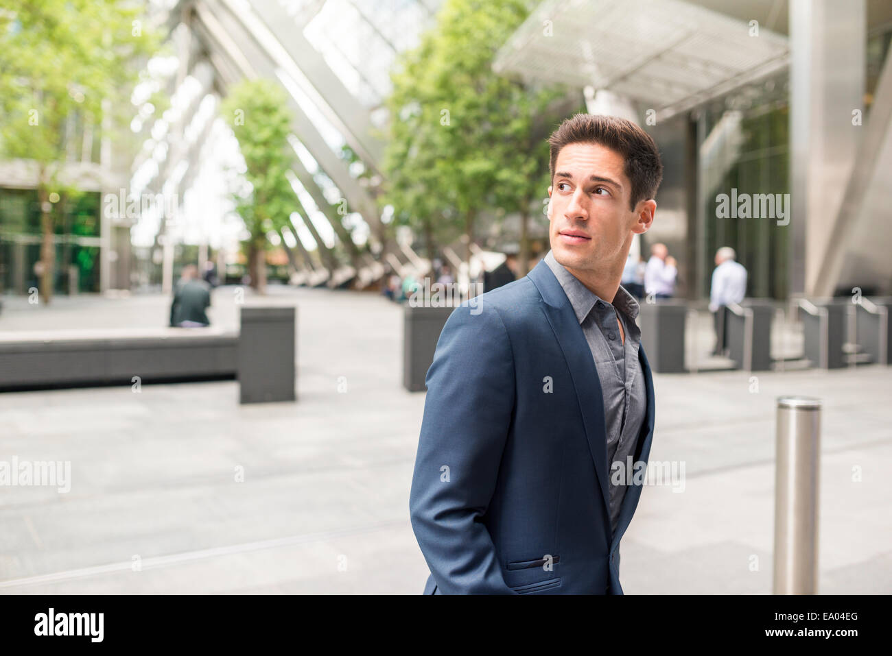 Young businessman looking over his shoulder at Broadgate Tower, London, UK - Stock Image