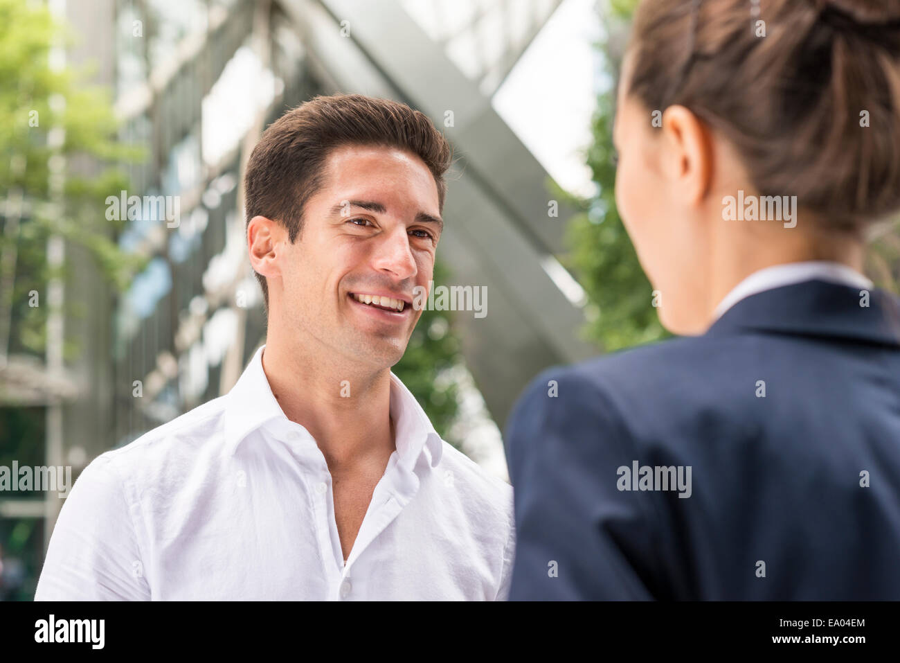 Young businessman and woman chatting at Broadgate Tower, London, UK - Stock Image