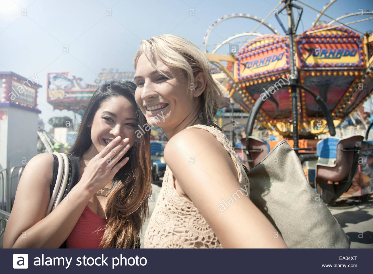 Two women at fairground, laughing and watching surroundings - Stock Image