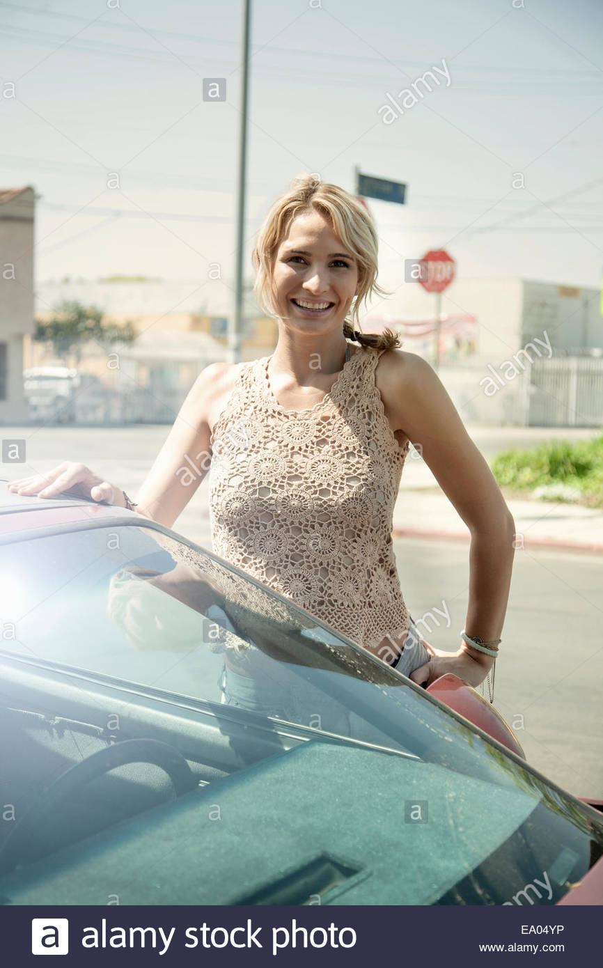 Portrait of young woman, standing beside car - Stock Image