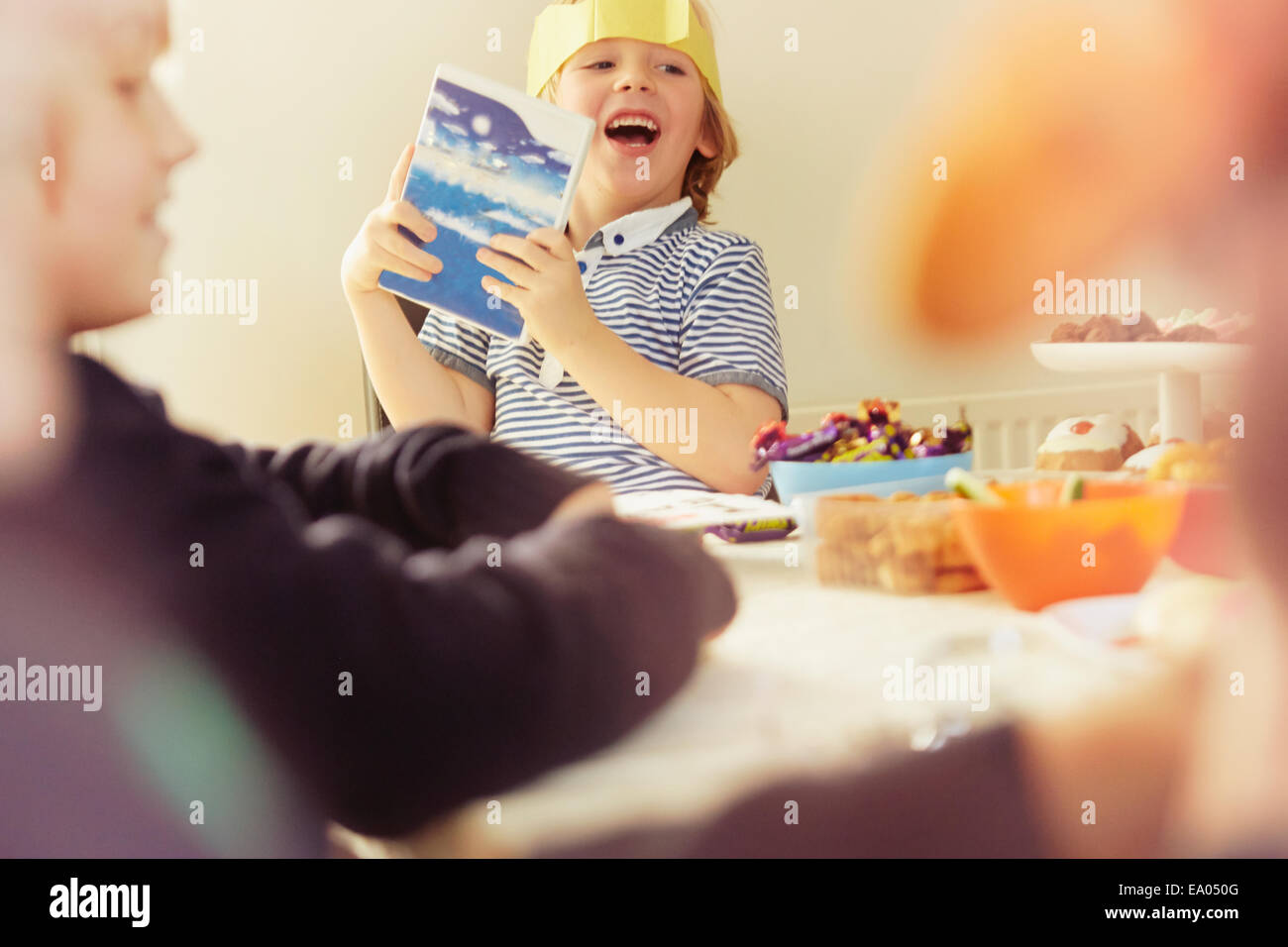 Young boy holding up opened Christmas present at table - Stock Image